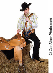 Cowboy with saddle and rein - Handsome young cowboy with...