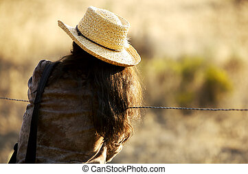 Cowgirl at the Fence - backside of a young cowgirl standing...