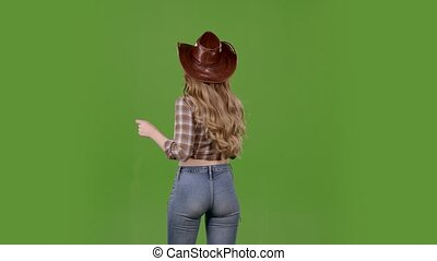 Cowgirl dances, standing with her back to the audience. Green screen