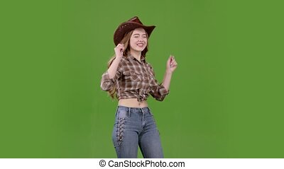 Girl in a cowboy hat is dancing different movements, the wind is waving her hair to the sides. Green screen