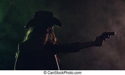 Cowgirl holds a revolver in her hands and aiming at the villain. Black smoke background. Slow motion. Side view. Silhouette