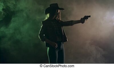Cowgirl holds a revolver in her hands and aiming at the villain. Black smoke background. Slow motion. Side view
