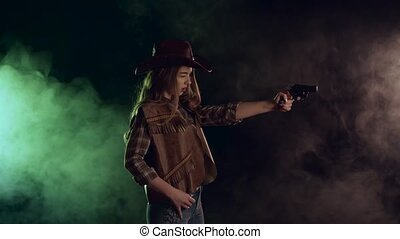 Cowgirl holds a revolver in her hands and aiming at the...