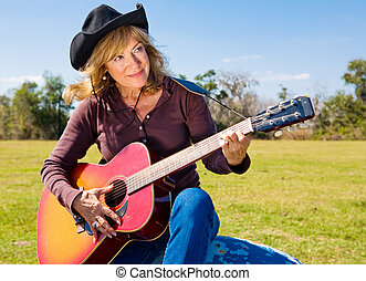 Beautiful mature singing cowgirl plays a song on her guitar.