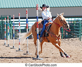 Cowgirl Pole Bending - Young cowgirl riding a palomino horse...