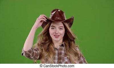 Cowgirl puts on a brown leather hat. Green screen. Slow motion