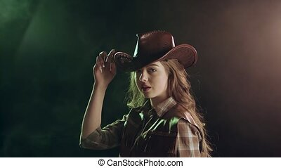 Cowgirl puts on a brown leather hat.Black smoke background. Slow motion