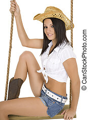 Cowgirl - Caucasian cowgirl in wooden swing on white...