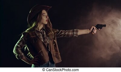 Cowgirl takes out a revolver and makes a shot. Black smoke background. Slow motion. Side view