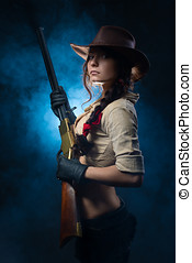 cowgirl with gun on a gray background - beautiful cowgirl...