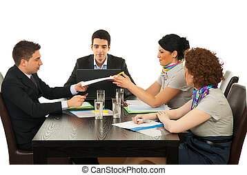 Four coworkers having cnversation and giving contract at meeting