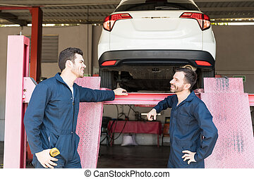 Coworkers Communicating Against Car Lift In Garage