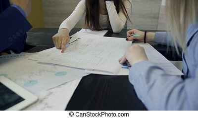 Coworkers discuss drawings sitting at the table in the office.
