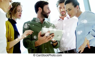 Coworkers discussing over digital tablet surrounded by white bubbles effect