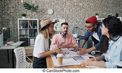 Coworkers having argument discussing business at work looking at building plan