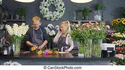 Coworkers in floral shop - Man in striped apron standing at...