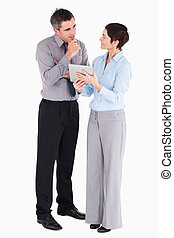 Coworkers looking at tablet computer against a white background
