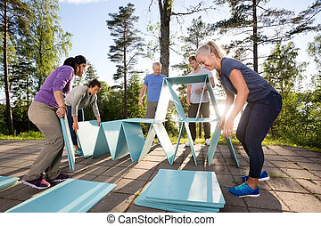 Coworkers Making Pyramid With Blue Planks On Patio - Male...