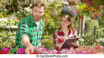Coworkers of flower fair in sunlight - Pretty woman with...