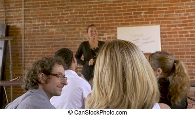 Coworkers smiling and attending an employee meeting on...