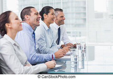 Coworkers smiling while listening to presentation in bright...
