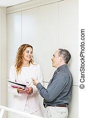 Coworkers talking in hallway
