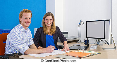 Coworkers - Two coworkers sitting behind a desk in front of...