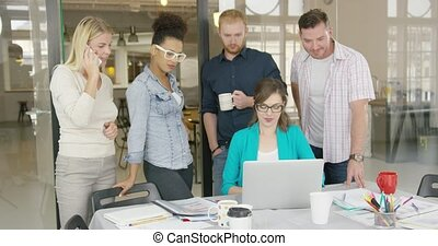 Coworkers watching laptop - Multiracial group of young...