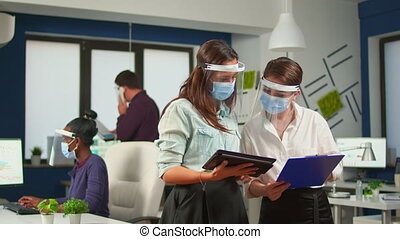 Coworkers with protection visor against coronavirus standing in new normal office comparing company financial datas holding digital tablet. Multiethnic business team working respecting social distance