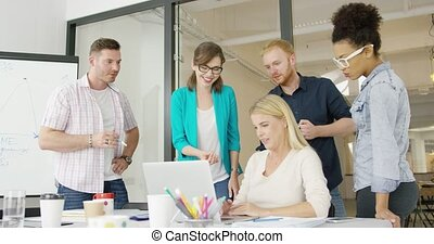 Coworkers with laptop in office