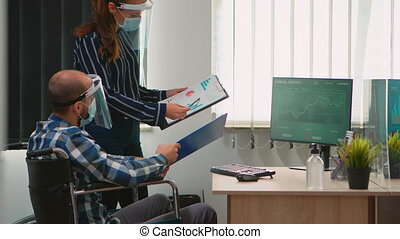 Coworkers with masks and visor working in new normal business office, businessman sitting in wheelchair respecting social distance. Team planning project in corporate company during covid-19 pandemic.