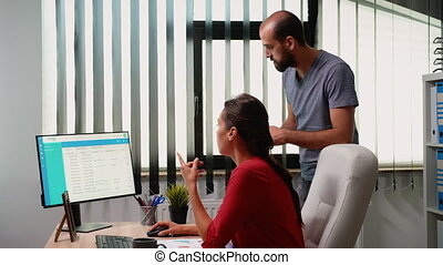 Young coworkers working together in modern office. Team discussing, talking, briefing consulting in professional, workplace in personal corporate company typing on computer keyboard looking at desktop