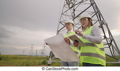 Coworking engineers with tablets on solar plant. Adult men...