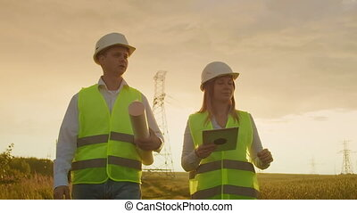 Coworking engineers with tablets on solar plant. Adult men ...
