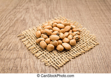 Cowpea legume. Grains on square cutout of jute. Wooden table. Selective focus.