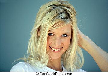 Coy blond woman touching hair
