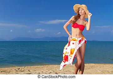 Coy blonde beauty in a red bikini showing her beautiful legs...