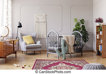 Cozy baby room with comfortable armchair with yellow pillow and grey wooden crib, real photo