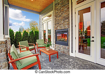 Cozy backyard deck with wooden furniture set and built in the wall fireplace