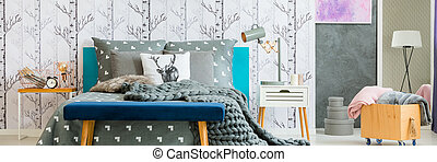 Lamp on white bedside cabinet and wooden box with blankets in cozy bedroom with king-size bed and blue stool