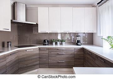 Cozy beige kitchen interior with wooden cupboards