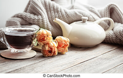 Cozy composition for Valentine's Day with a cup of tea, flowers and a knitted element.