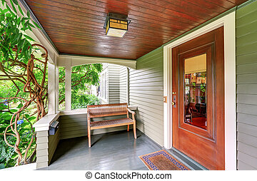 Cozy covered porch interior with wooden bench.
