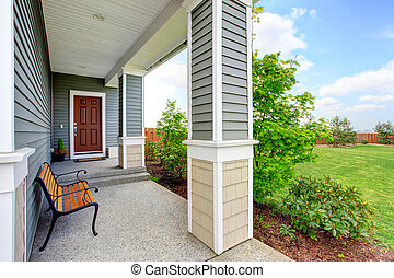 Cozy covered porch with concrete floor, columns and comfortable bench