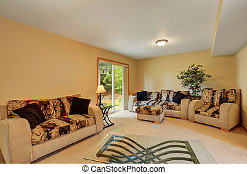 Cozy family room in warm peach and beige tones. Comfortable sofa set with colorful cushions and modern glass coffee table. Doors to backyard. Northwest, USA