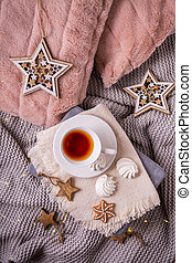Cozy home and hygge concept with cup of tea and Christmas cookies,  warm blanket