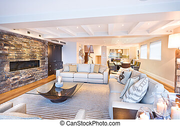 Cozy living room with several sofas placed in front of a stone wall with a fireplace