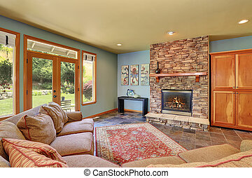 Cozy living room with blue walls and stone tile fireplace.