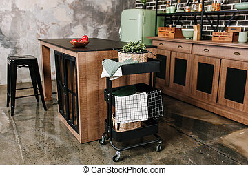 Cozy loft kitchen with dinning table, chairs and metal storage racks on wheels - trolley