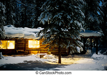 Yukon/Alaska trapline log-cabin fully illuminated at full-moon night in snowy winter.
